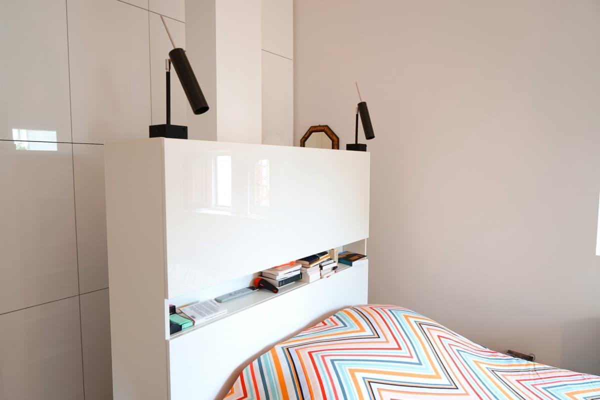Ensemble placard ouvert qui sait jouer le rôle de tête de lit - En fond on distingue un large placard fermé, le tout dans un esprit minimaliste et épuré