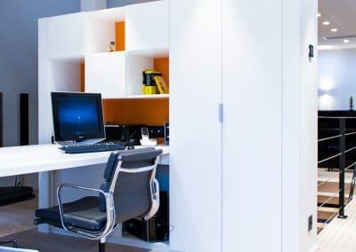 Un espace bureau en îlot - Façade blanche et fonds orange laqué - Aménagement d'une porte pliante pour accès aisé au contenu des étagères