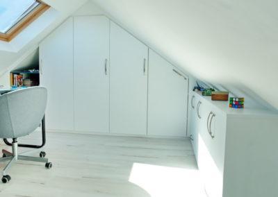 agencement blanc pour l'optimisation du rangement dans ce bureau sous pente